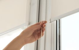 Woman opening modern roll blinds on window in room, closeup