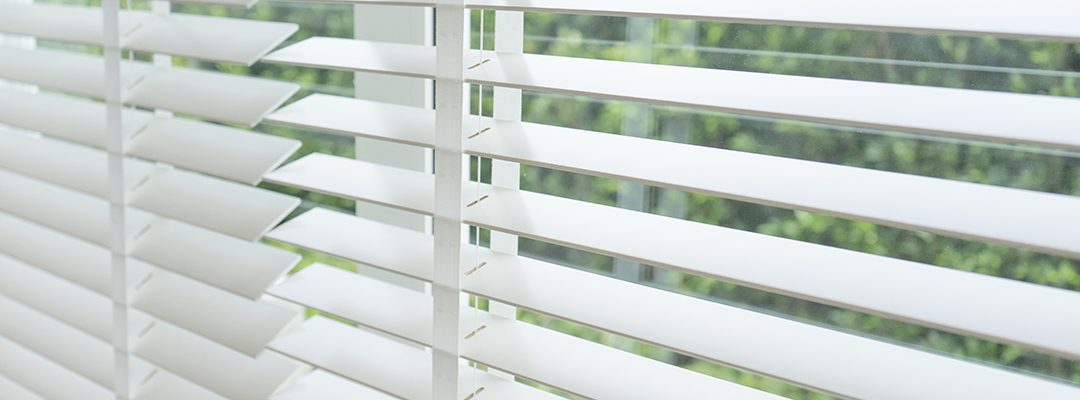 Close up view of window with horizontal blinds. White Roller Bli